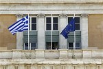 Men adjust flags at the facade of the Greek parliament in Athens